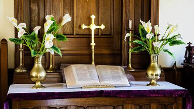 easter lilies in church with cross