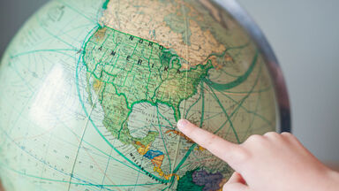child pointing to Florida on a globe