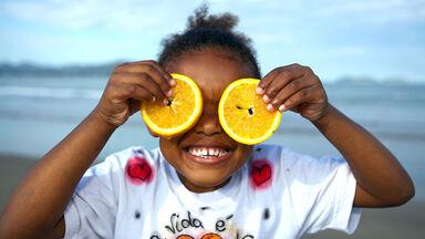 girl holding Florida orange slices over eyes
