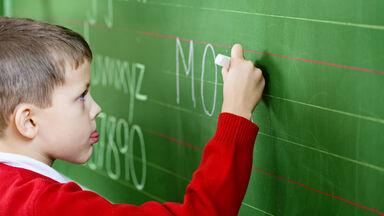 boy writing chalkboard assess vocabulary