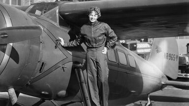 Amelia Earhart next to aircraft
