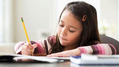 girl working on plural noun worksheet