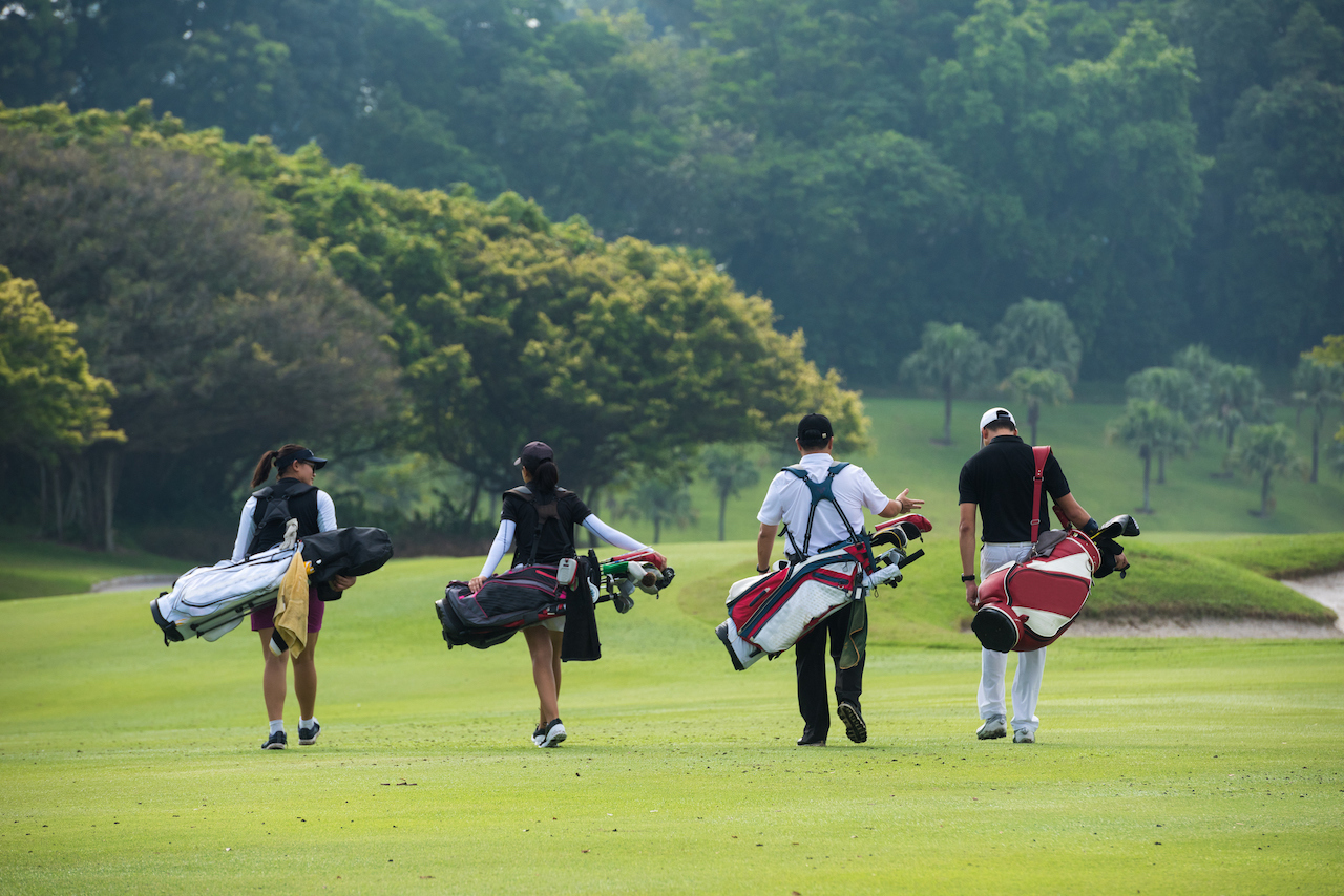 golfers walking with bags on course