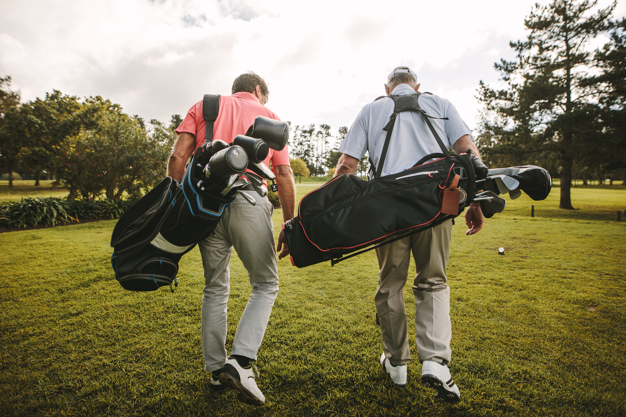 Two golfers carrying golf bags