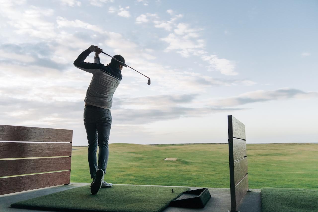 Man swinging club at driving range