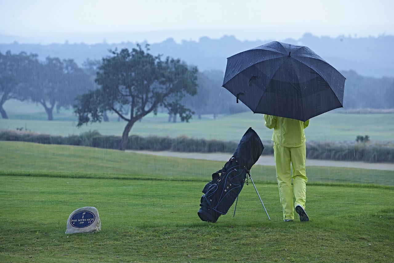 Golfer with golf umbrella in the rain