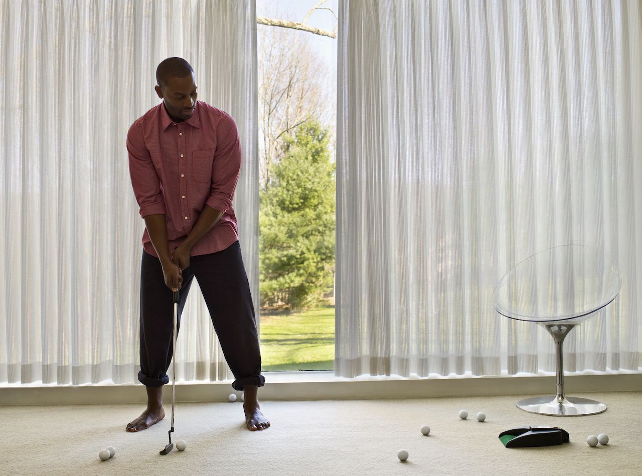 man practicing putting at home