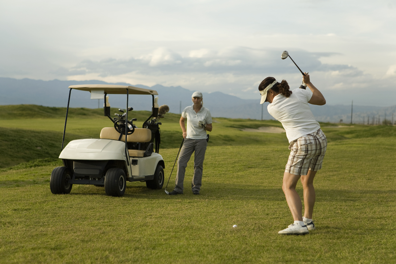woman watching golfers swing