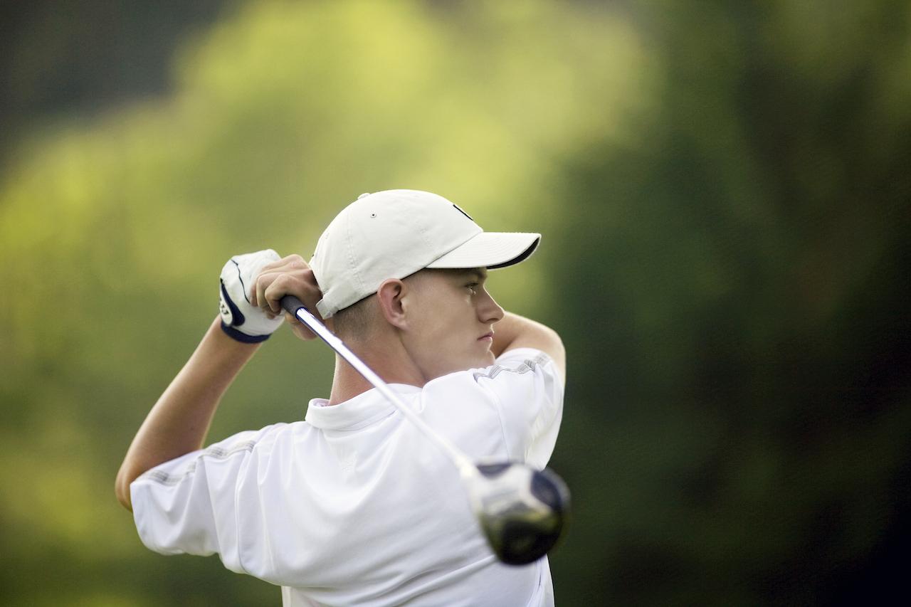 Golfer wearing white hat during swing
